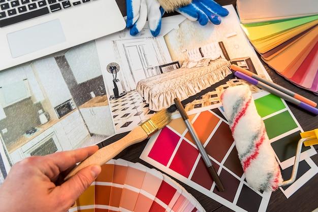 デザインホームのカラーサンプラーで男性の手作業。オフィスデスクでのアパートのスケッチ