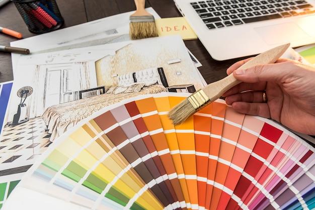 남성 손은 디자인 홈을 위한 색상 샘플러로 작업합니다. 사무실 책상에 아파트 스케치