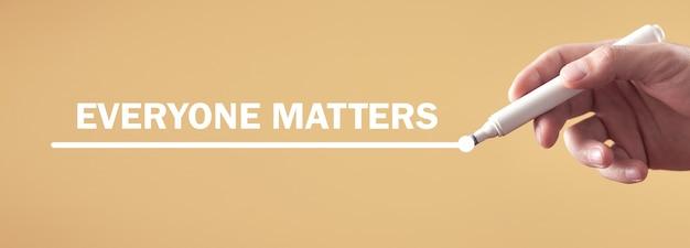 남성 손은 화면에 everyone matters 텍스트를 씁니다.
