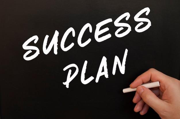 男性の手が黒板に「成功計画」という言葉をチョークで書く