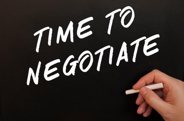 男性の手が黒板に「交渉する時間」という言葉をチョークで書く