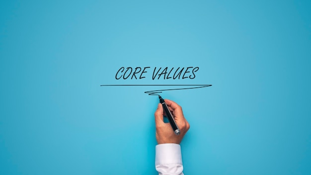 Male hand writing core values sign over blue background with black marker. Premium Photo