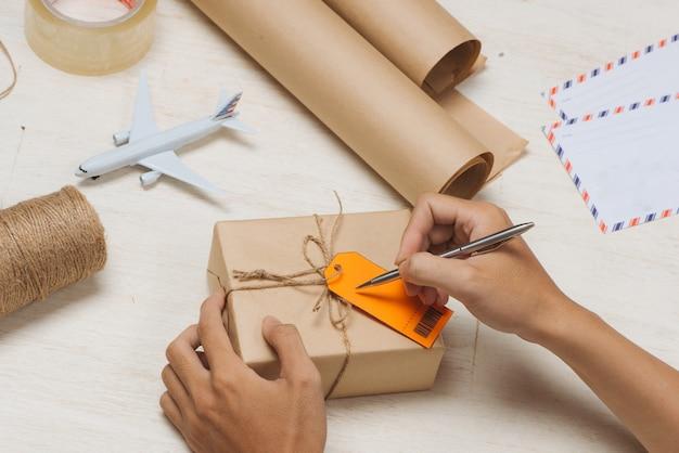 茶色の紙の小包の荷物タグに男性の手書き
