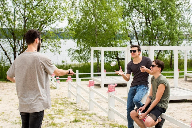 Male handing beer to friends