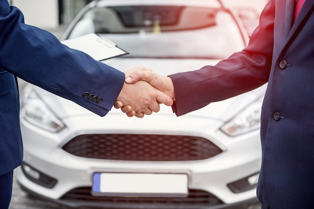 Male hands against car, making handshakes close up