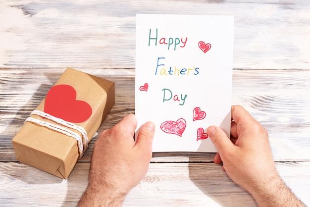Мужские руки держат поздравительную открытку, сделанную ребенком