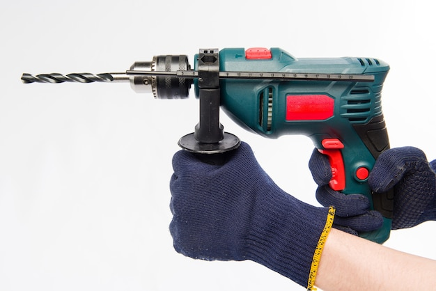 Male hands are holding an electric drill