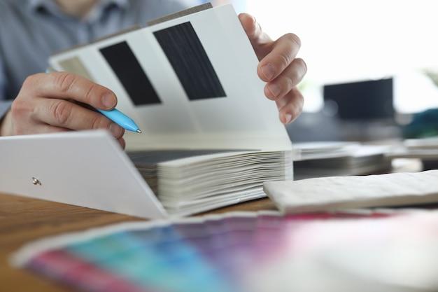 男性の手はペンと仕上げ材のサンプルを持っています。インテリアデザイナーのコンセプトのサービス