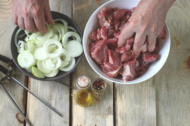 男性の手がバーベキュー用の肉片を持っています生のオニオンリング