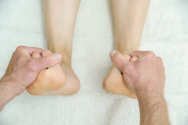 Male hands are massaging feet.
