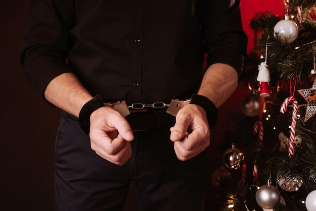 Male hands in bdsm handcuffs for submission and domination against the background of a christmas tree on new year's holiday
