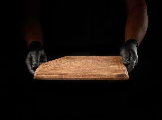 Male hands in black latex gloves hold an empty vintage brown wooden chopping board