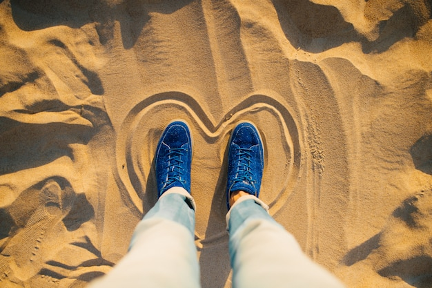 Male hands in blue jeans and stylish sneakers standing inside painted heart on sand.