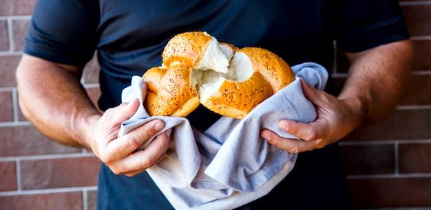 Male hands breaking freshly baked bread, closeup.