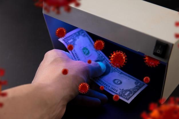 남성의 손이 감지기에서 지폐를 확인하고, 코로나바이러스의 3d 모델이 주위에 퍼집니다. 감염의 위험이 높습니다. 판데믹, 전염병, 우리가 일상에서 볼 수 없는 질병과 질병.