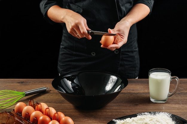 Male hands chef chefs break the egg on a wooden brown table in a black bowl