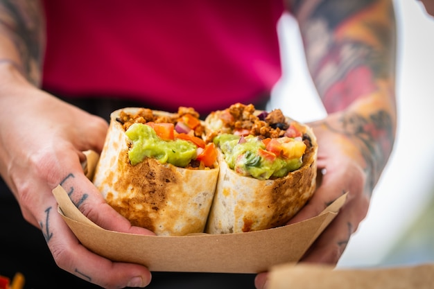 The male hands of a chef in a fast food cafe hold a burrito with minced meat