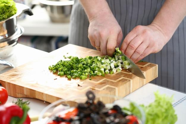 Male hands chopping salad scallion ingredient