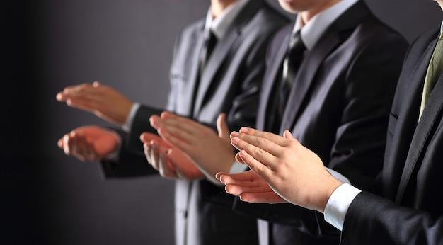 Мужские руки хлопают в ладоши на черном, вид сбоку