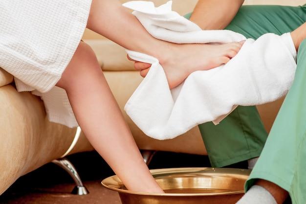 Мужские руки, чистящие ногу женщины.