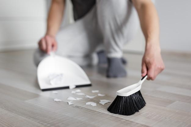 거실에서 국자와 브러시로 찢어진 종이 조각을 청소하는 남성 손