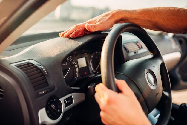 Мужские руки чистят авто, полировка приборной панели на автомойке. мужчина натирает торпеду автомобиля полиролью.