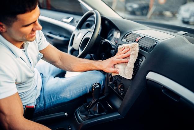 Мужские руки чистят авто, полировка приборной панели автомобиля