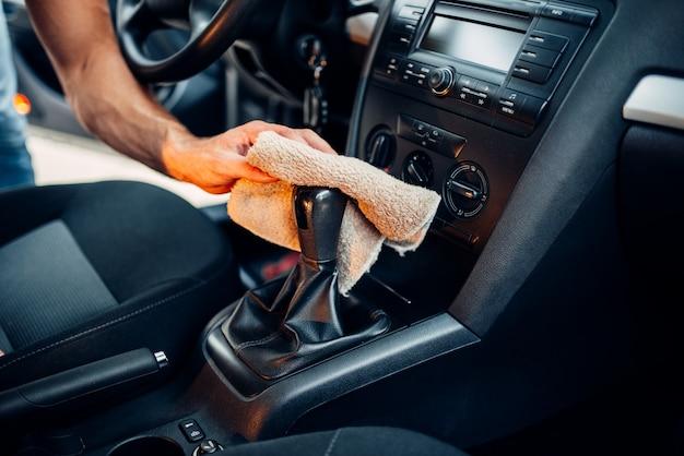 男性の手は洗車ステーションの車内をクリーンアップします。自動車クリーニング