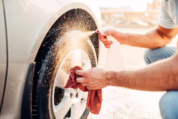 男性の手は車のリムクリーナー、洗車でディスクをきれいにします。洗車ステーション