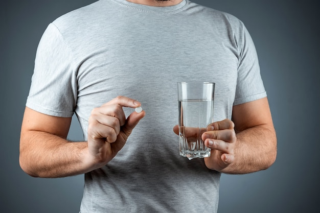 Male hands close-up, holds a glass of water and a pill, medication, treatment, gray wall. medical theme, vitamins, health care.