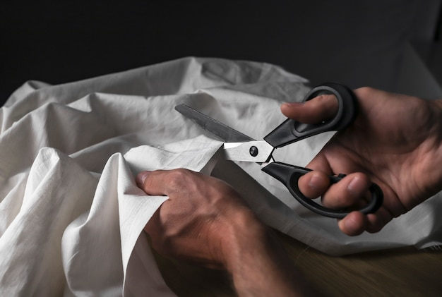Male hands closeup cutting beige cotton or linen cloth with sewing scissors