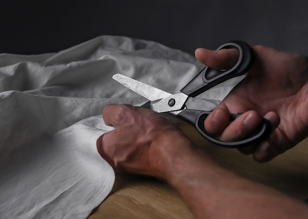 Male hands closeup cutting beige cotton or linen cloth with sewing scissors.