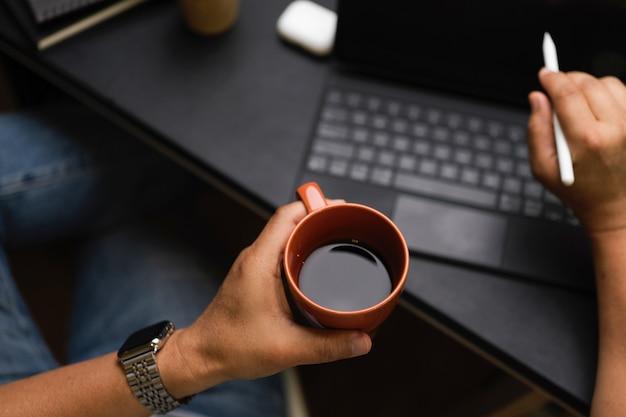 남성 손 클로즈업은 블랙 커피를 들고 백그라운드에서 블랙 테이블에 있는 디지털 태블릿 작업