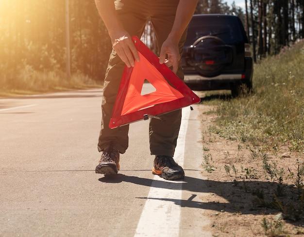 여름에 부서진 차 근처 도로변에 빨간색 삼각형 주의 표시를 하는 남성 손 클로즈업
