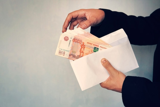 남성의 손은 루블을 5,000 루블로 액면가로 간주합니다. 흰 봉투에 돈입니다. 검정색 배경에 봉투에 루블 뇌물.