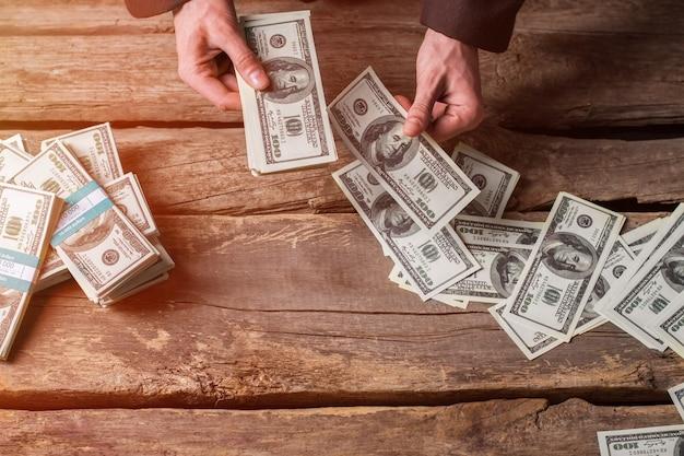 달러를 세는 남성 손. 갈색 나무 배경에 현금. 당신이 얻은 모든 것. 사업가에게 좋은 보상.