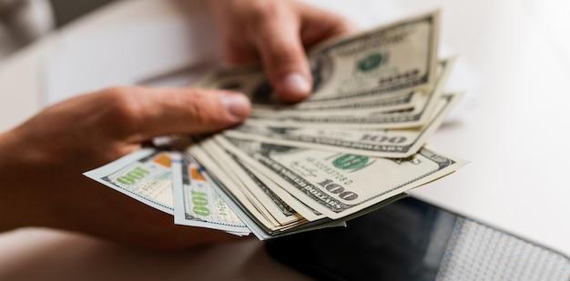 男性の手は私たちにドル札を数えるか、投資成功の背景概念を現金で支払う...