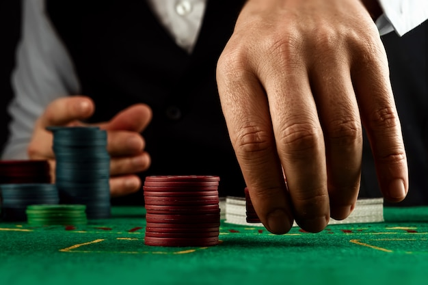 男性の手はカジノでディーラーになり、緑の布のクローズアップでチップを再生します