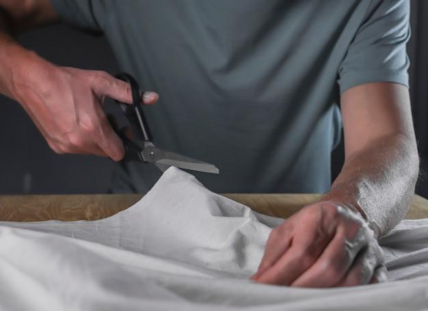 Мужские руки, режущие хлопчатобумажную ткань швейными ножницами