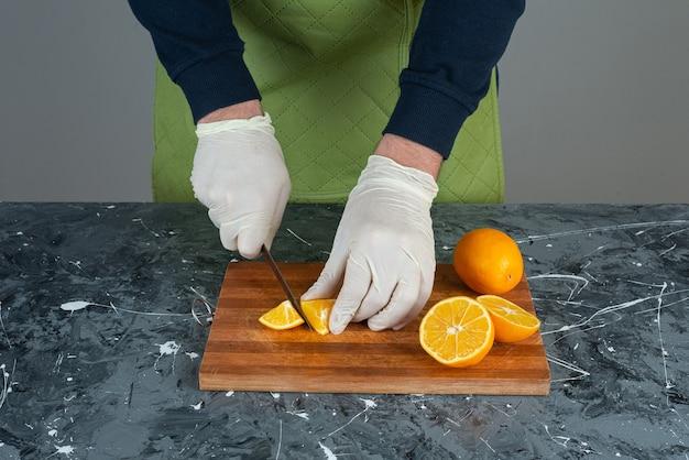 Mani maschii che tagliano il limone fresco sulla tavola di marmo.