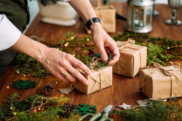 木製のテーブルにモミの枝でホリデークラフトギフトボックスを飾る男性の手