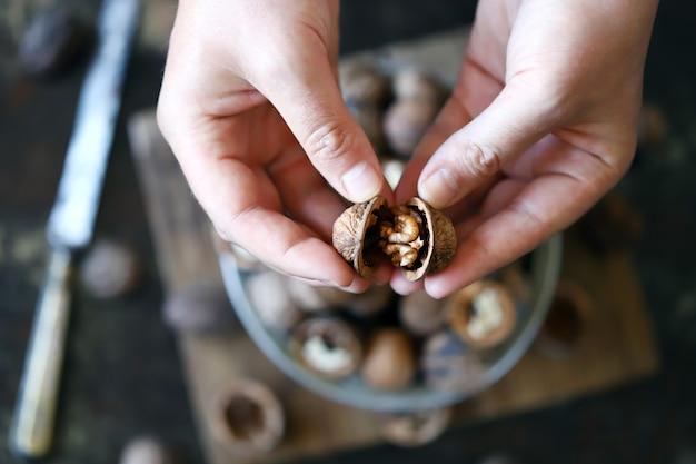 男性の手は殻からクルミを抽出します