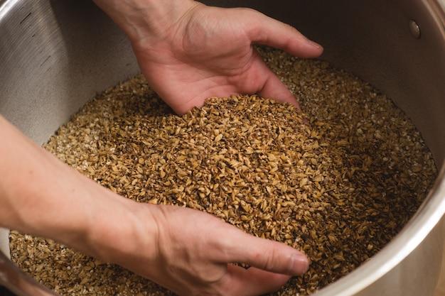 Мужские руки, из которых выливается молотый солод. хорошее отношение к ремеслу