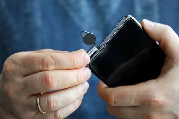 그의 스마트 폰의 sim 카드 슬롯을 받고 남성 손