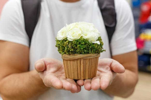 남성의 손에 꽃 냄비를 잡고 있습니다. 저장소에서 선물 쇼핑 개념