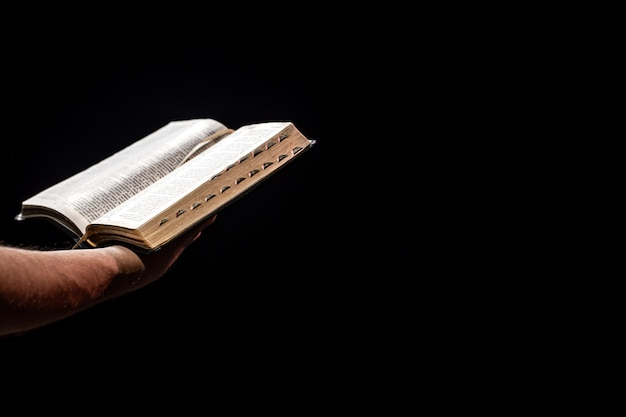남성의 손은 어둠 속에서 열린 성경을 들고 있습니다. 믿음의 개념과 하나님과의 개인적인 관계.
