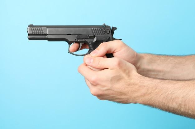 Male hands hold black pistol on blue