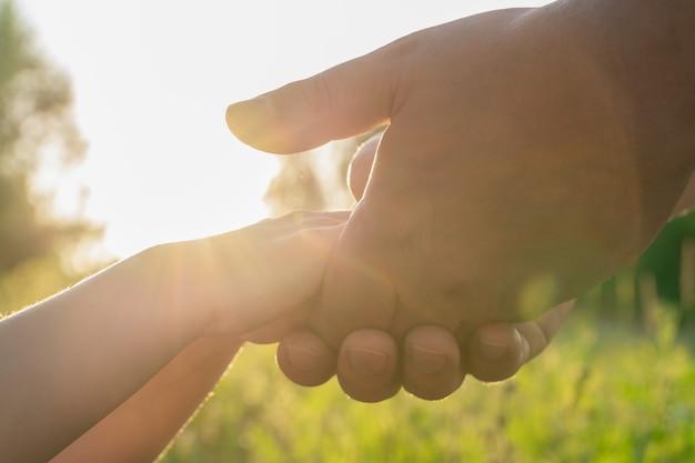 Мужские руки держат детские руки в ладонях солнце зажигает твои руки