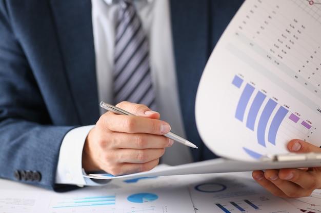 Мужские руки держат документы с финансовой статистикой