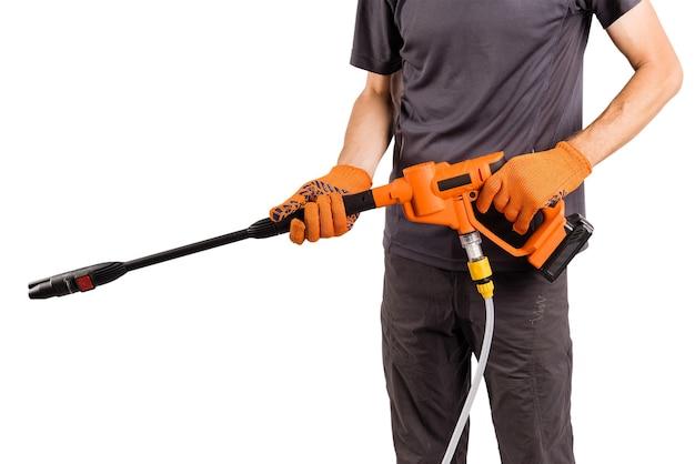 男性の手は家庭用工具高圧水力洗濯機を保持します
